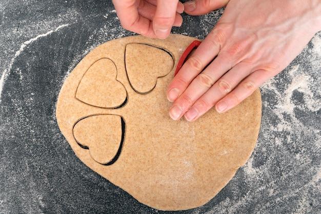 ハート型の生地を作る女性の手。ショートブレッドクッキーを作るプロセス。