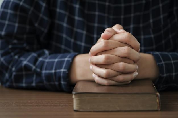 女性の手は聖書で神に祈る善を信じるテーブルの上で手をつないで祈る