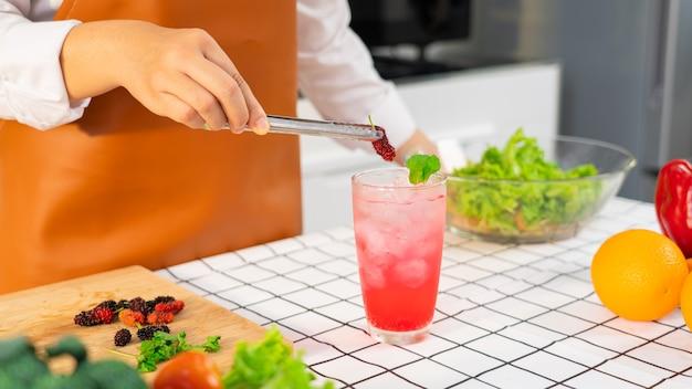 여성은 아이스 핑크 색상 음료와 함께 달콤한 뽕나무를 잔에 넣어 미리 페어링 목 테일을 손에 넣습니다.