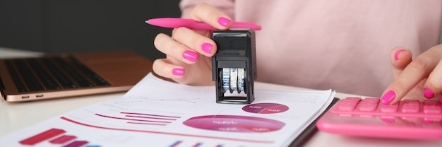 Women hands put stamp on documents and count on calculator