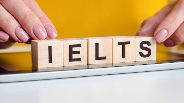 Women hands puts a wooden blocks with the letters ielts on the black surface of the notepad