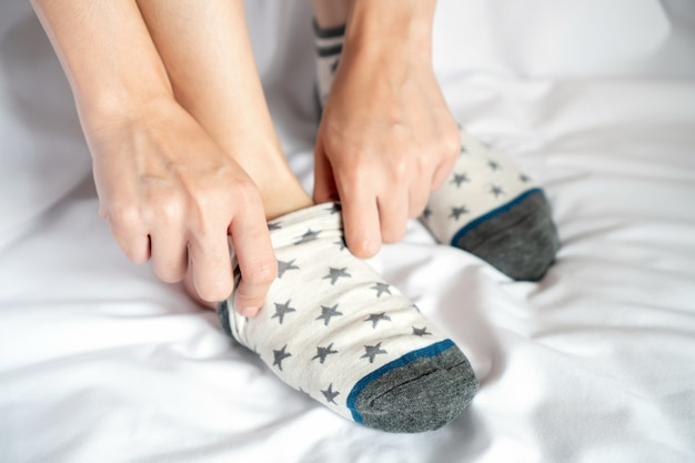 Women hands to putting on pastel cotton socks on white fabric floor.