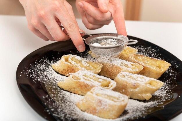Женские руки посыпают яблочный рулет сахарной пудрой. корм для штруделя.