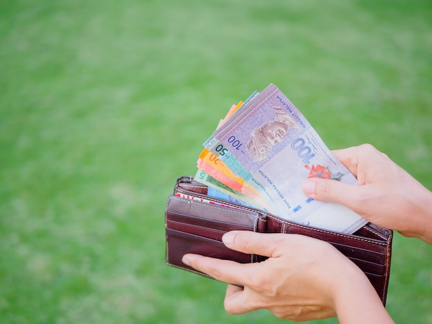 Women hands taking out money malaysia ringgit from wallet.