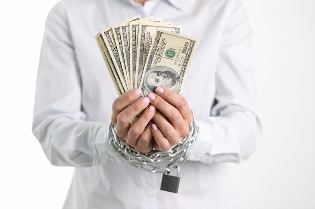 チェーンで結ばれた女性の手は、購入とローンへの100ドル紙幣中毒を保持します