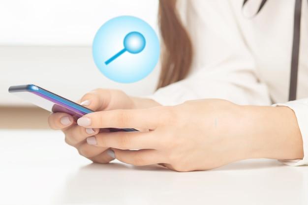 Женские руки с мобильным телефоном и значком поиска