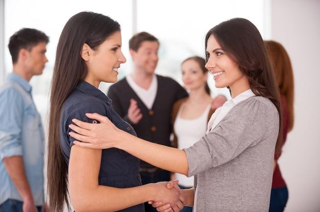 Женщины рукопожатия. две веселые молодые женщины обмениваются рукопожатием, пока группа людей общается на заднем плане