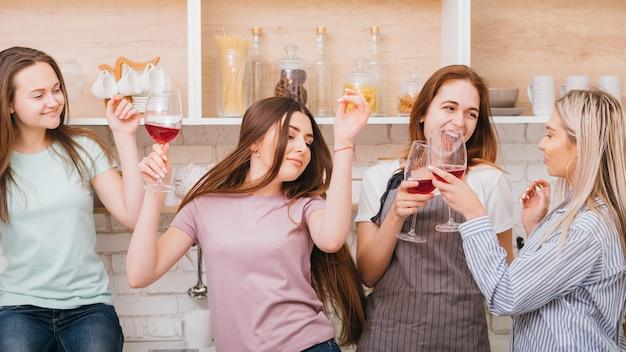 ぶらぶらしている女性。カジュアルなパーティーの楽しみ。アルコールの乱用。赤ワインを飲むのに楽しい時間を過ごしている若い女性。