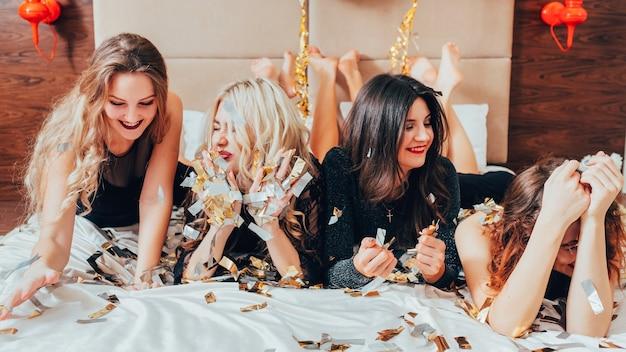 여성은 즐거운 시간을 보냅니다. 함께 즐거운 시간을 보내십시오. 침대에 누워 즐거운 젊은 여성의 행. 처녀 파티. 주위에 색종이.