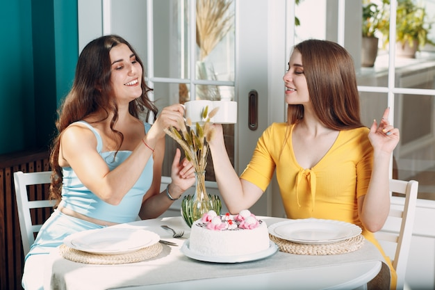 Women happy friends at home sitting and smiling with white birthday cake and cup of tea.