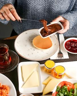 女性はチョコレートクリームとパンケーキで朝食をとる