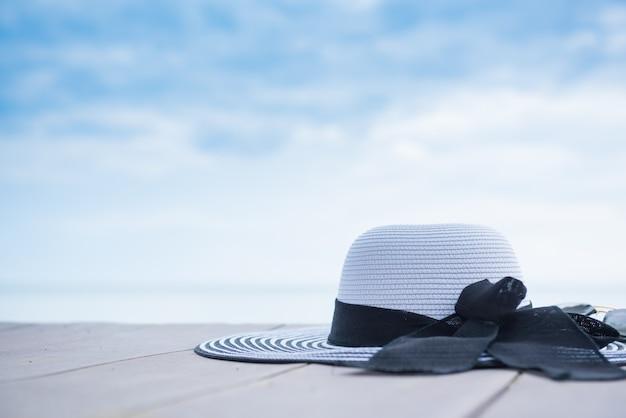ビーチで女性の帽子。青い空を背景にスペースのある夏休み。