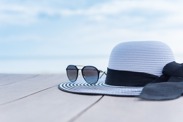 Женская шляпа на пляже. летние каникулы с космосом на фоне голубого неба.