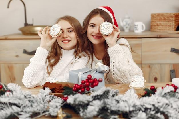 여자들은 컵 케이크를 가지고 있습니다. 크리스마스 장식에서 친구. 산타의 모자에있는 소녀.