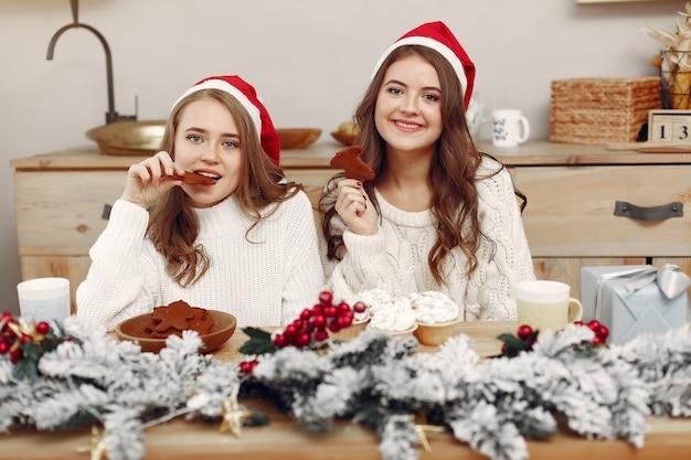 У женщин есть кексы. друзья в рождественских украшениях. девушка в шляпе санты.