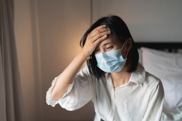여성은 침실에 아프고 수술 용 마스크를 쓰고 있습니다.