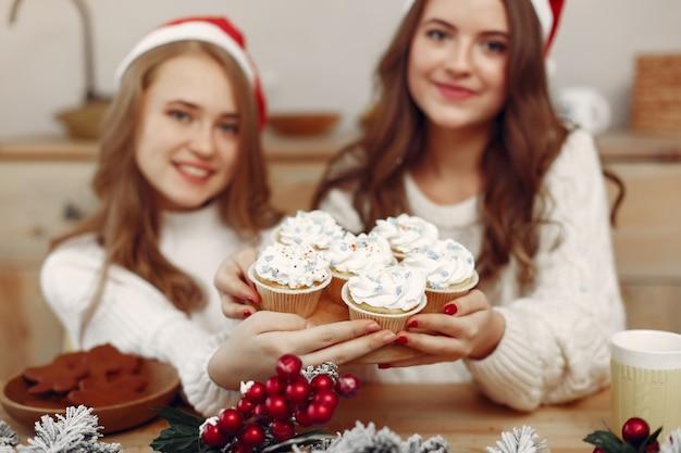 Le donne hanno un dolcetto. amici in decorazioni natalizie. ragazza con il cappello di babbo natale.