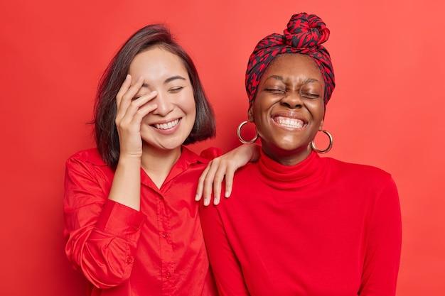 여성들은 즐겁게 웃고 흰색 완벽한 치아를 보여주고 선명한 빨간색에 캐주얼 옷을 입는다