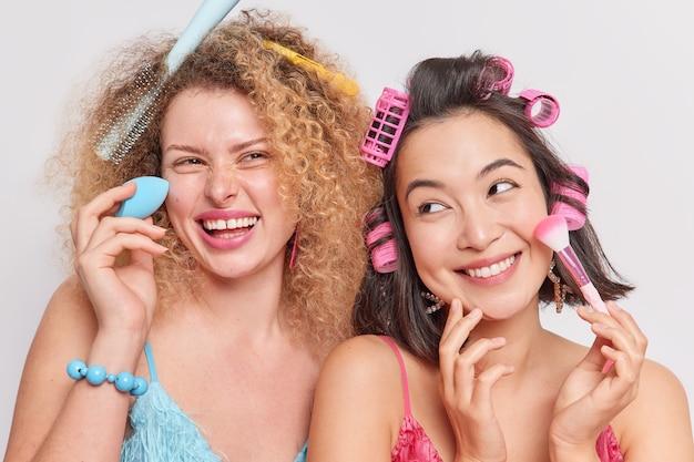 女性は幸せな表情を持っているファンデーションを適用する化粧品のツールを使用して髪型をパーティーウェアの準備をする白で隔離されたファッショナブルなドレス