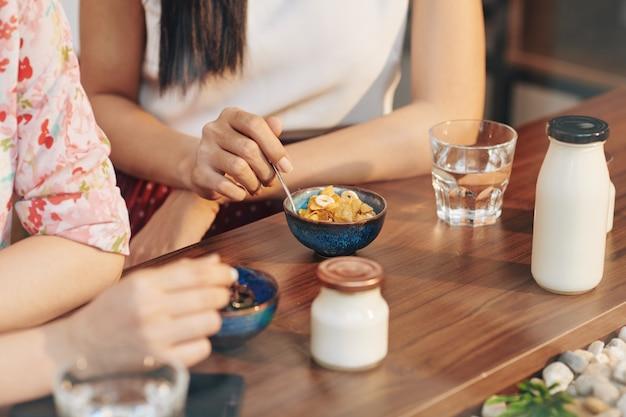 コーンフレークとヨーグルトを食べる女性