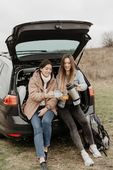 Women having tea on road trip break