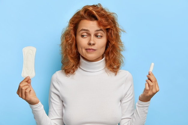 Women health care and hygiene concept. indoor shot of hesitant young ginger woman holds two intimate products, chooses between tampon and pad during menses, thinks what gives better protection