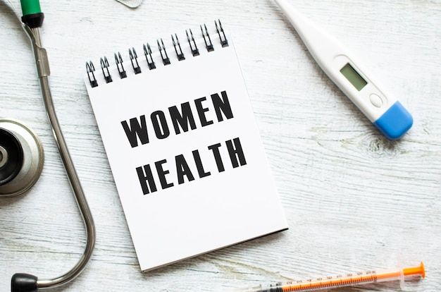 Women health is written in a notebook on a light wooden table next to a stethoscope