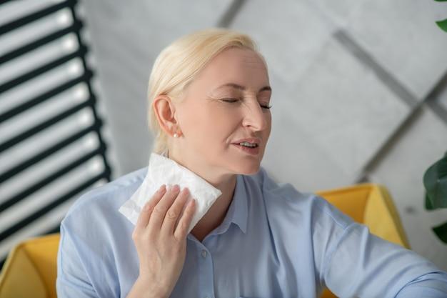 여성 건강. 실내에서 그녀의 목 근처에 냅킨을 들고 내리는 눈꺼풀이있는 밝은 파란색 블라우스에 여자.