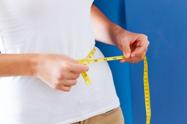 테이프 측정 또는 측정 테이프를 사용하여 허리 지방을 측정하는 여성 건강한 바디 케어 체중 조절.