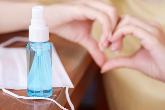 女性の彼女の手とクリーニングと医療用サージカルマスク用の青いアルコールジェルボトル。武漢コロナウイルスとエピデミックウイルスの症状の汚染を避けるために、細菌、細菌、ウイルスを取り除き、殺します。