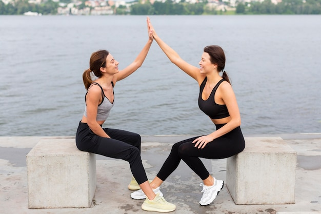 Women high-fiving each other while exercising outdoors