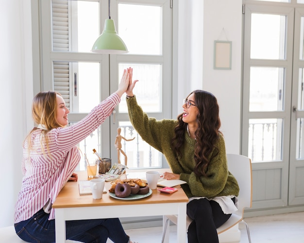Women high-fiving over table