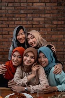 Женщины в хиджабе позируют вместе, смотрят в камеру