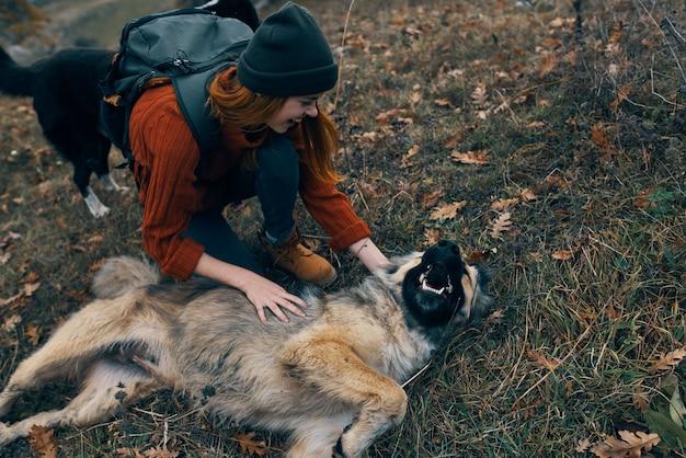 自然の中で犬をかわいがる女性ハイカー