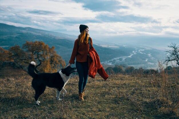 自然の中で犬と散歩をしている女性ハイカー