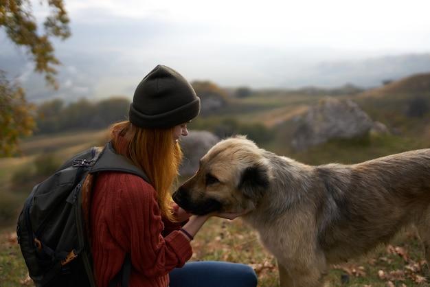 Путешественники женщины гуляют с собакой на природе