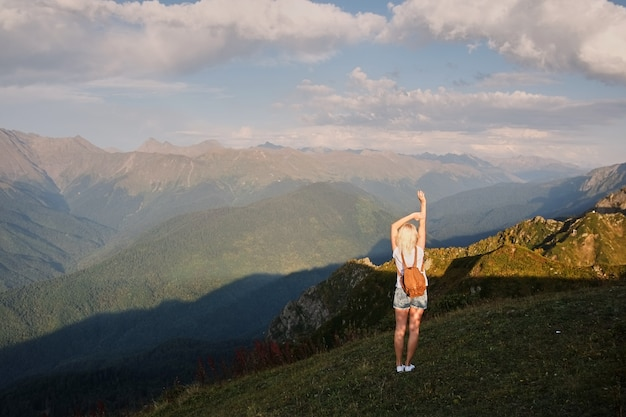 Women hiker with backpack is climbing the ridge mountains