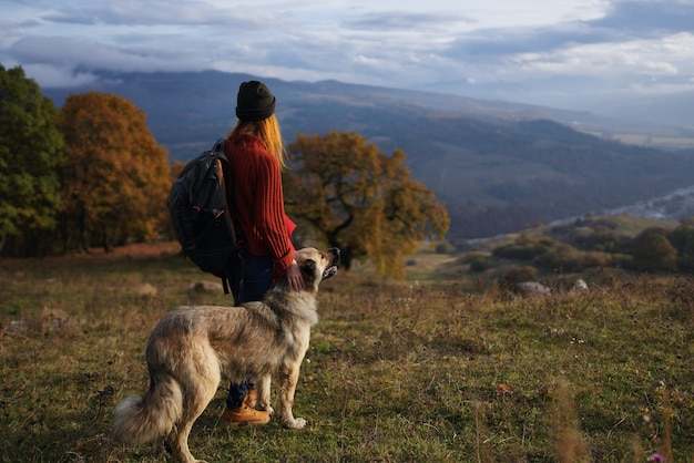 犬の散歩山の秋の森の隣の女性ハイカー