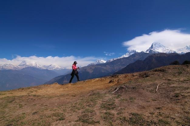 夏には山を上るトレッキングスティックを持ったバックパックでハイキングをしている女性が雪で覆われています。短時間休憩中の風景観察