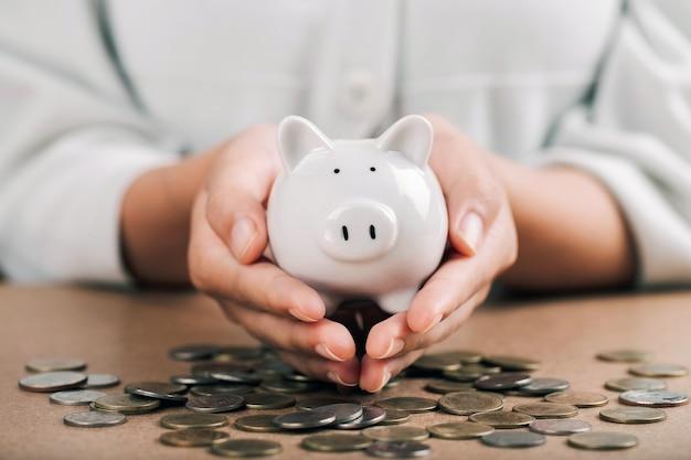 女性はコインの上に貯金箱を持っており、将来の投資コンセプトのためにお金を節約しています。