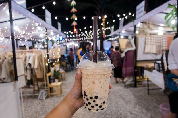 Women hold bubble tea at walking street on night.