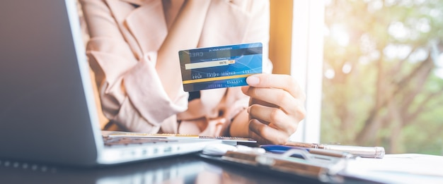 Женщины держат кредитные карты, чтобы делать покупки в интернете с портативного компьютера. для веб-баннера.