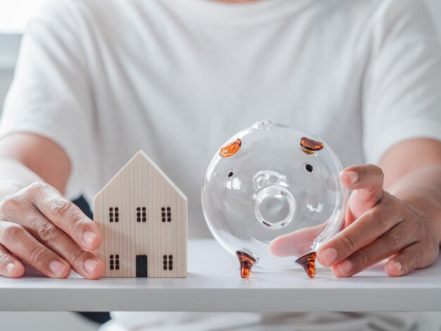 Women hold home model and piggy bank on the white table
