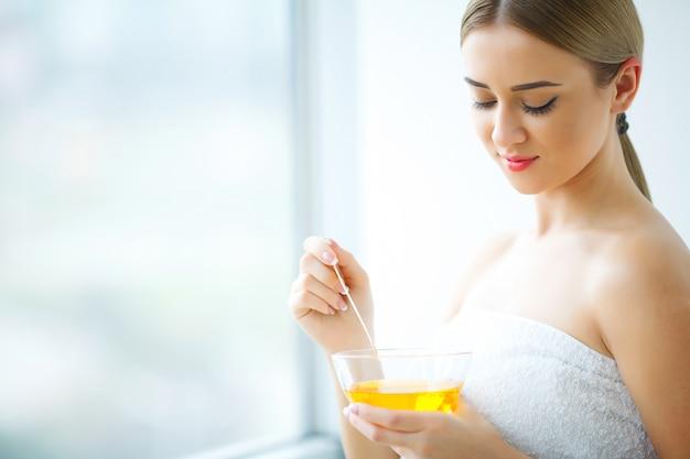 Women hold orange paraffin wax bowl, woman in beauty salon