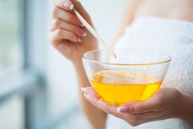 Women hold orange paraffin wax bowl. woman in beauty salon