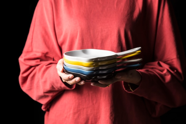 Women hold plates in their hands.