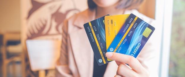 女性は3つのクレジットカードを持っています。ards.webバナー用。