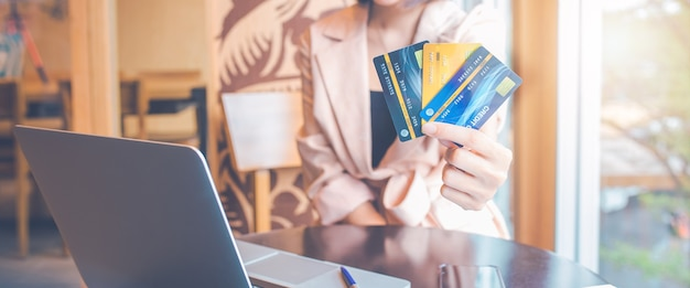 Women hold three credit cards to shop online.for web banner.