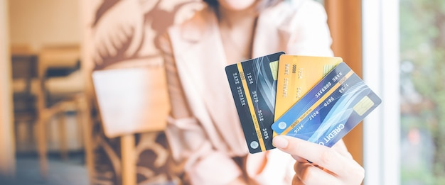 Women hold three credit cards to shop onlinefor web banner