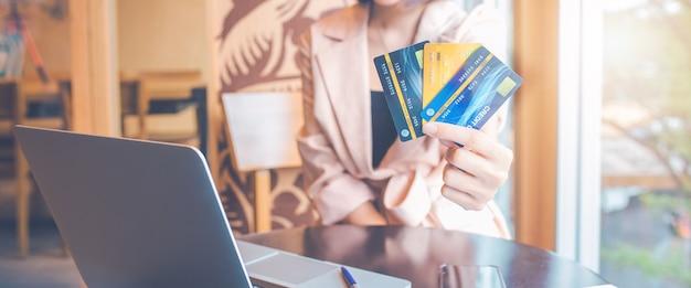 女性はオンラインで買い物をするために3枚のクレジットカードを持っています。ウェブバナー用。